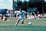 Men's Soccer game athlete #21 dribbling ball